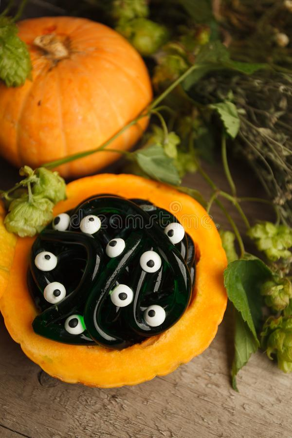 Spooky Halloween party food - gummy jelly worms in pumpkin with monsret eyes on wooden background, holiday party close up royalty free stock photo