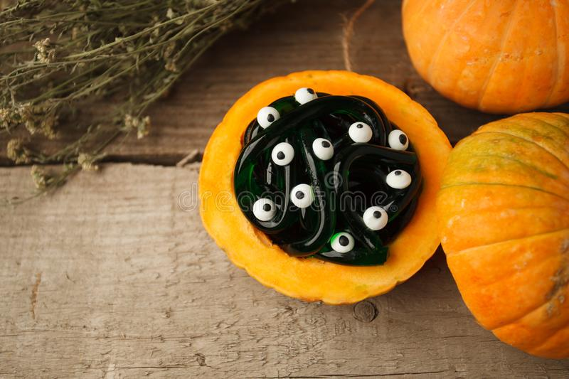 Halloween, junk food and confectionery concept - green and black multicolored gummy worms and candies eyes with pumpkin royalty free stock photography