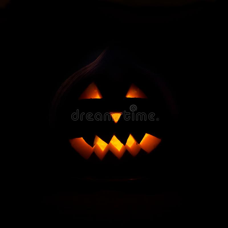The spooky Halloween pumpkin face. With dark background and glowing eyes royalty free stock image