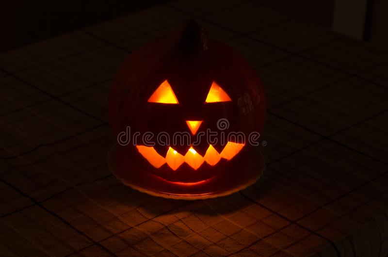 The spooky Halloween pumpkin face. With dark background and glowing eyes on the table stock images