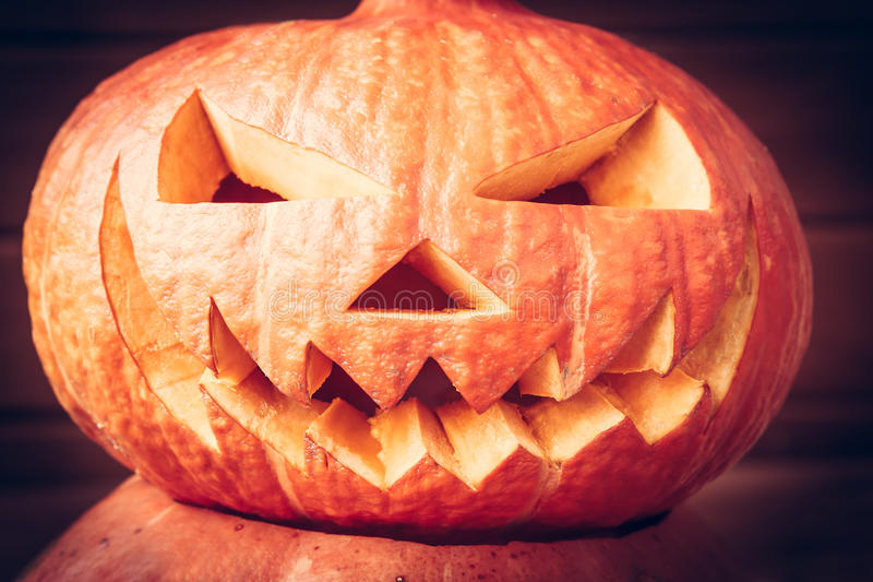 Spooky halloween pumpkin face on dark background. Scary halloween pumpkin face on dark background royalty free stock images