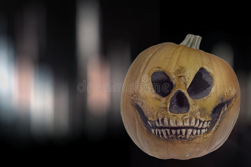 Spooky halloween pumpkin. In the form of a human skull against a mysterious background royalty free stock image