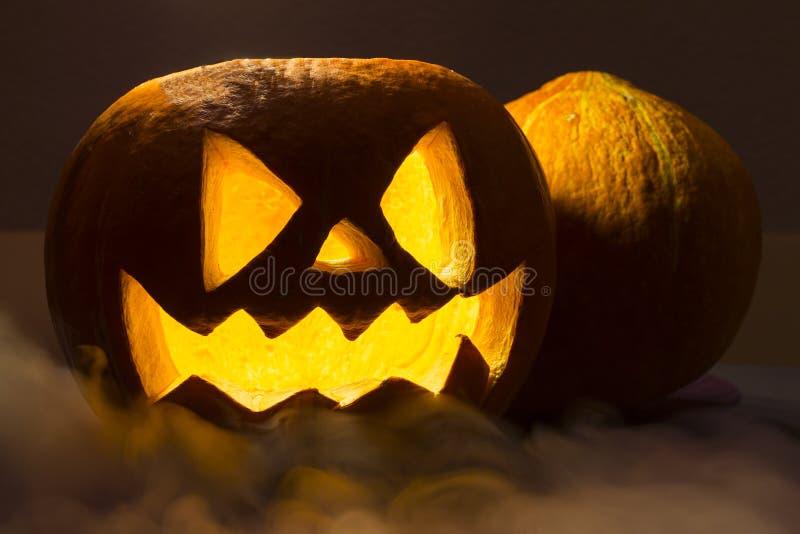 Spooky halloween pumpkin with the smoke on the dark background. Spooky orange halloween pumpkin with the smoke on the dark background stock images