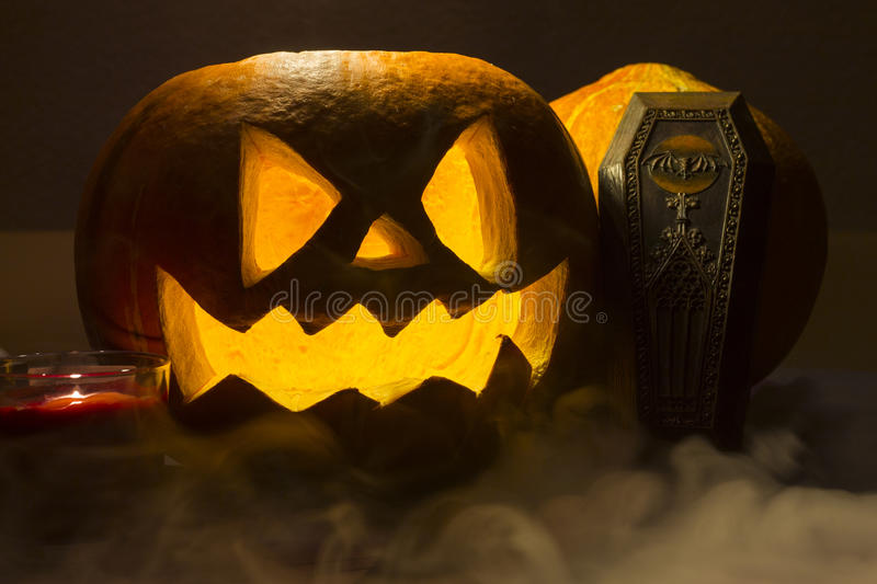 Spooky halloween pumpkin with the smoke on the dark background. Spooky orange halloween pumpkin with the smoke on the dark background royalty free stock photography