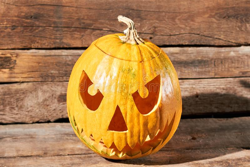 Spooky Halloween pumpkin on wooden background. stock images