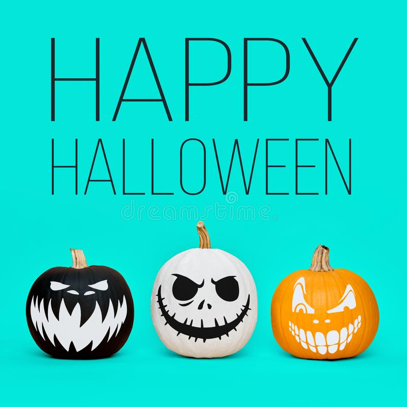 Spooky Halloween pumpkins with scary face expressions over pastel blue background. Halloween concept. Three Spooky Halloween pumpkins with scary face stock photography