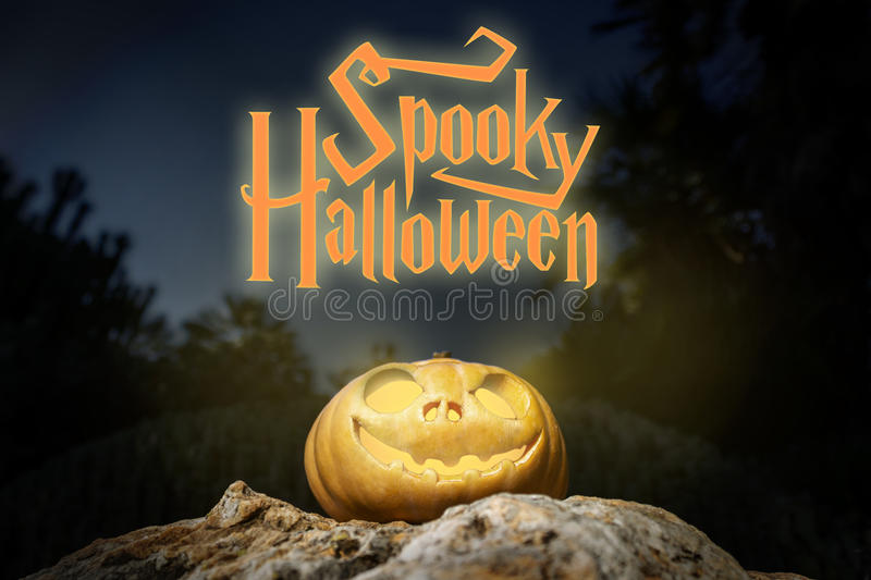 Spooky Halloween warm neon pumpkin in on a rock in the darkness. Spooky Halloween warm neon and scary pumpkin jack-o-lantern with a smile on a rock from bottom royalty free stock photography