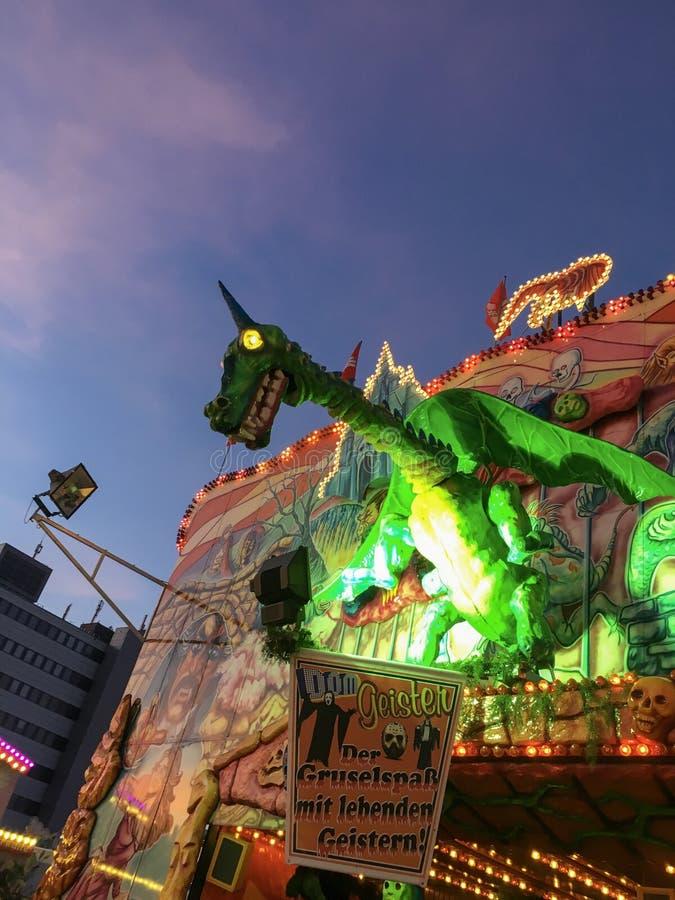 Spooky Horned Green Dragon met gele gloeiende ogen - Ghost Train Puppet/Animatronic over German Funfair Hamburger Dom royalty-vrije stock foto's