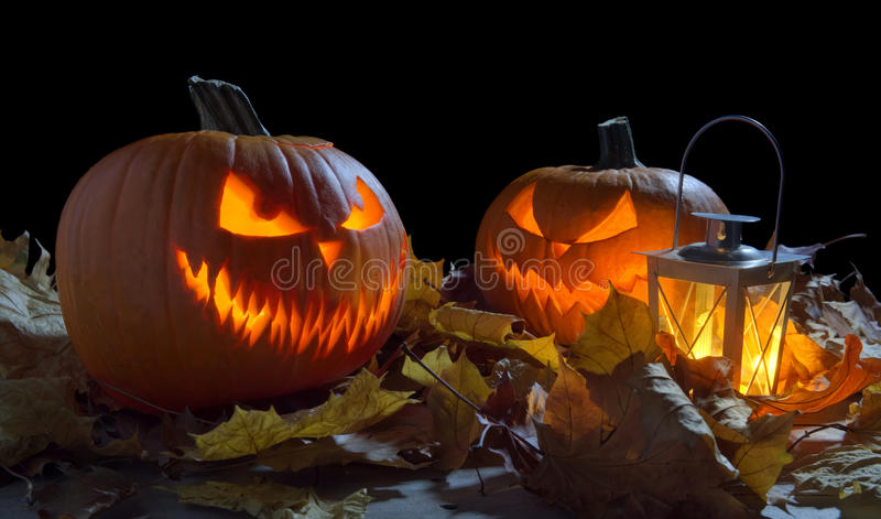 Spooky jack o lantern among dried leaves on black royalty free stock images