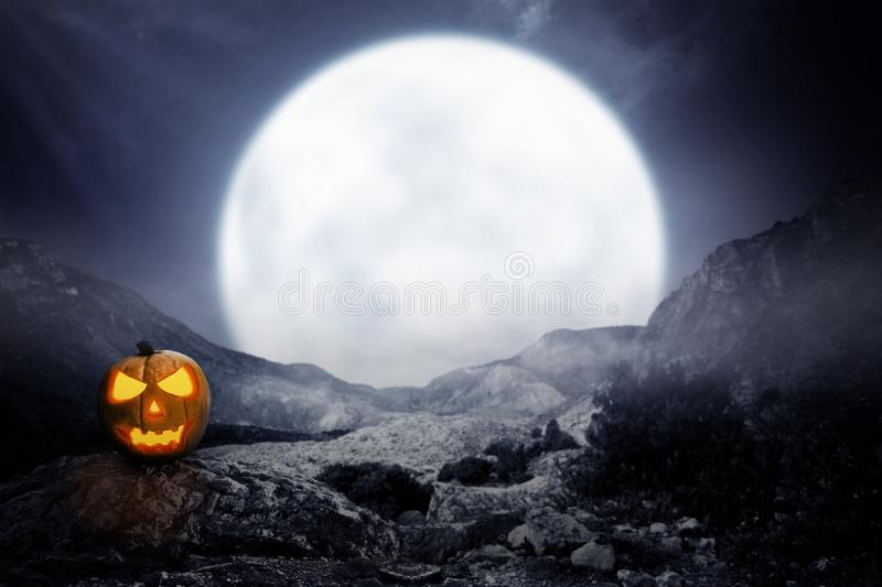 Spooky jack-o-lantern on rocky mountain. With moon background royalty free stock photography