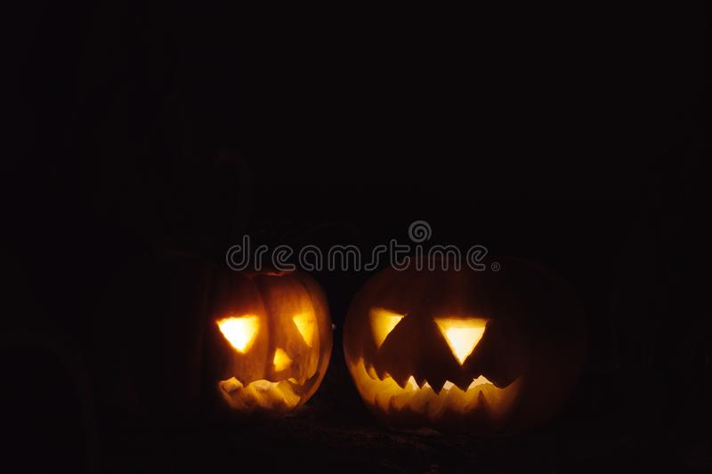 Spooky and laughing carved Halloween Jack-o-lantern pumpkins. With lights isolated over dark background - with copy space royalty free stock image