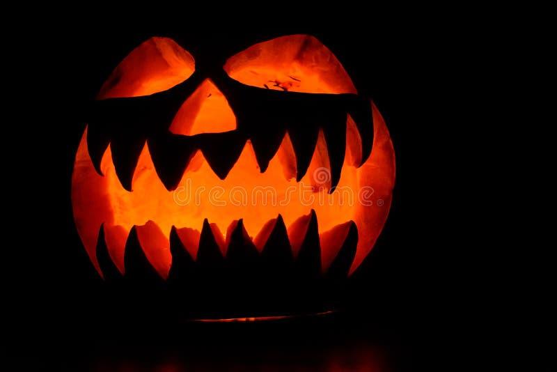 Spooky halloween pumpkin on a black background. Spooky luminous halloween pumpkin on black background royalty free stock photo