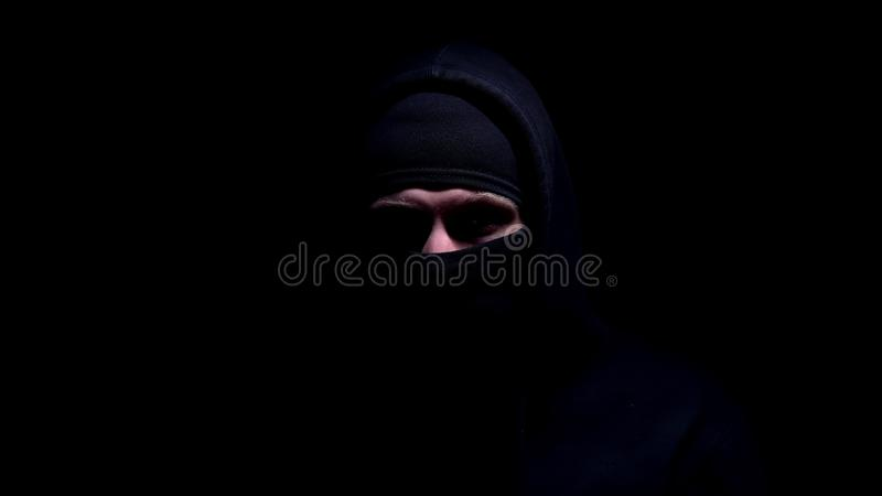 Spooky man in balaclava and hood looking into camera, member of gangster group. Stock photo stock photos