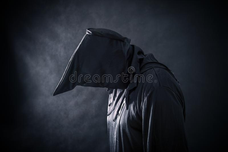 Spooky monster in hooded cloak. In the darkness royalty free stock photo