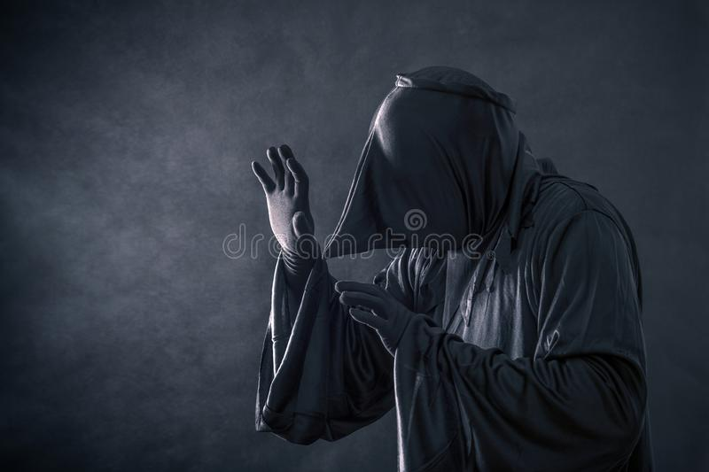 Spooky monster in hooded cloak. In the darkness stock photo