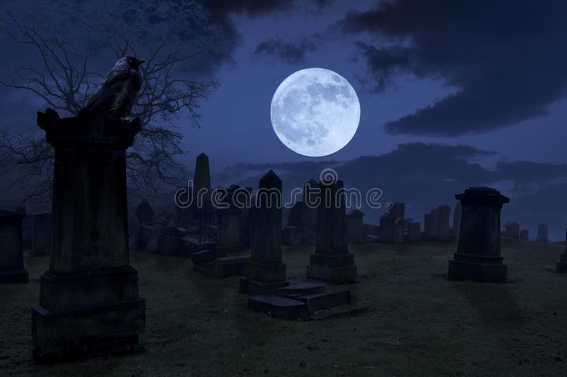 Spooky night at cemetery with old gravestones, full moon and black raven stock images