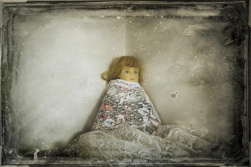 A spooky old doll, rapped in vintage net curtains. With a moody grunge edit stock photos