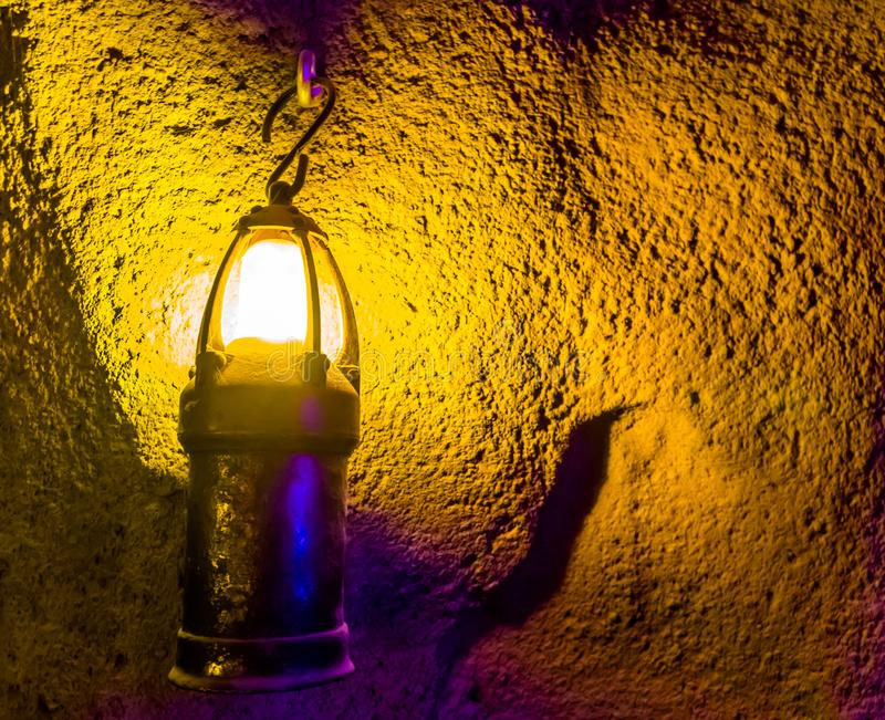 Spooky old lighted lantern hanging on the wall of a underground cave, scary halloween background, Vintage objects. A spooky old lighted lantern hanging on the stock photo