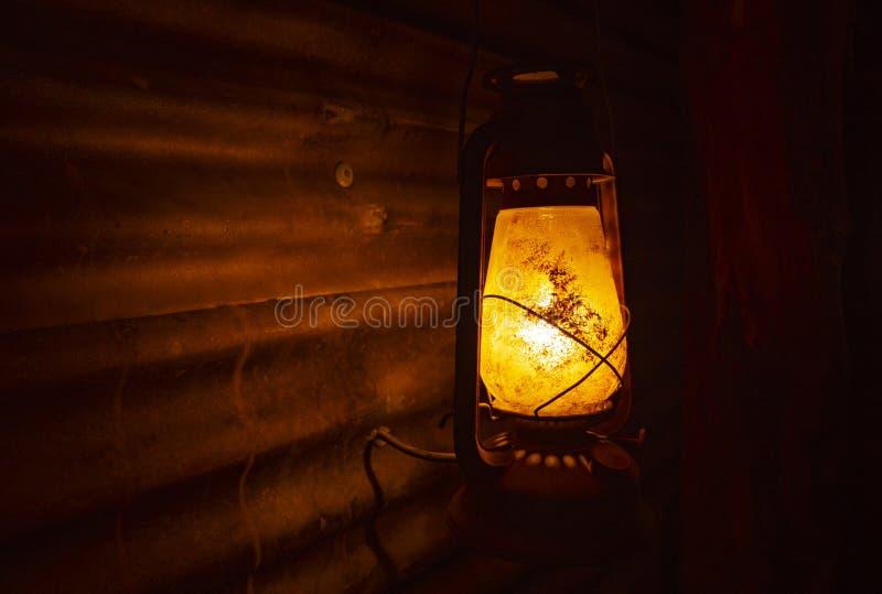 Old rustic kerosene lantern lamp with copy space. Spooky old retro kerosene lantern lamp with light cast on corrugated iron wall and dark black background royalty free stock photo