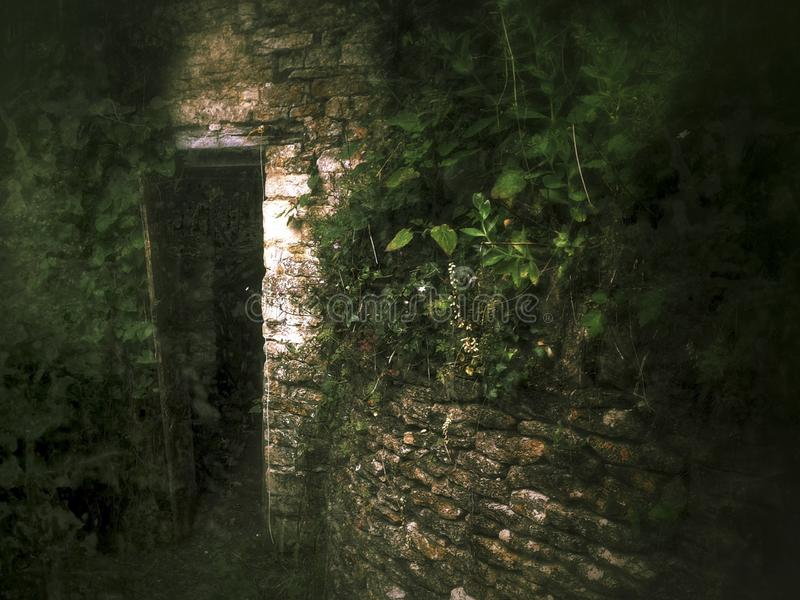 Spooky open door to an old stone outbuilding royalty free stock photo