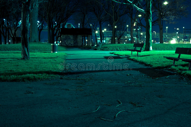Spooky park at night. A spooky park at night in autumn with path and benches. Illuminated by streetlights royalty free stock photography