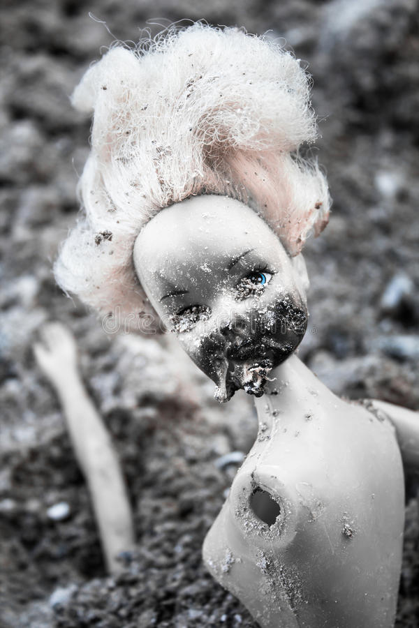 Spooky plastic doll on the pile of ash stock image