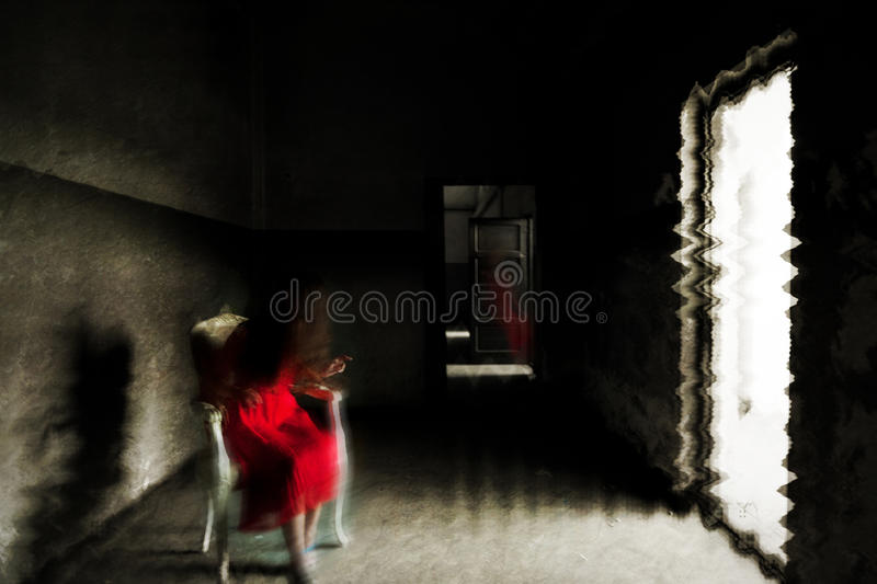 Spooky poltergeist moment with a ghost girl. Ghost of a girl in red dress in the light. Grunge interior stock photography