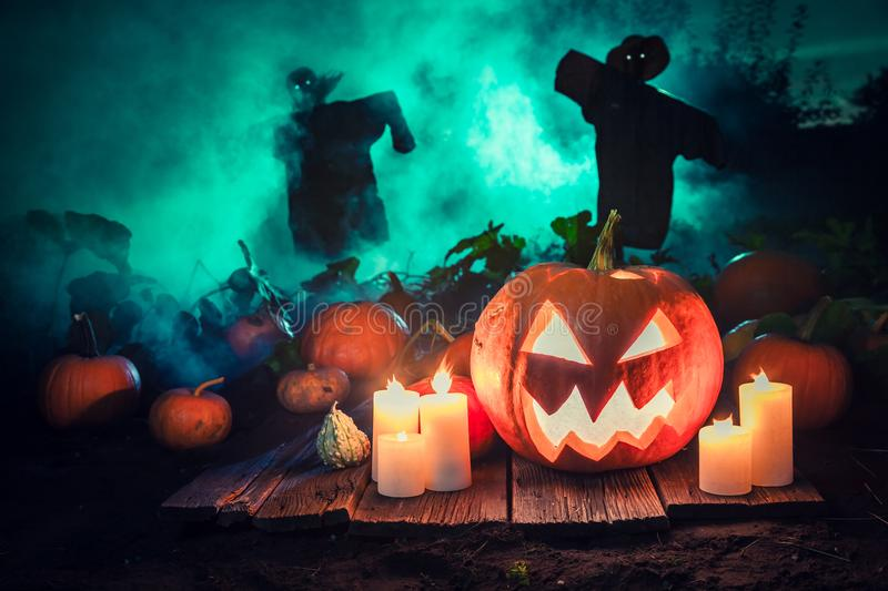 Spooky pumpkin with green mist and scarecrows for Halloween. On dark background stock image