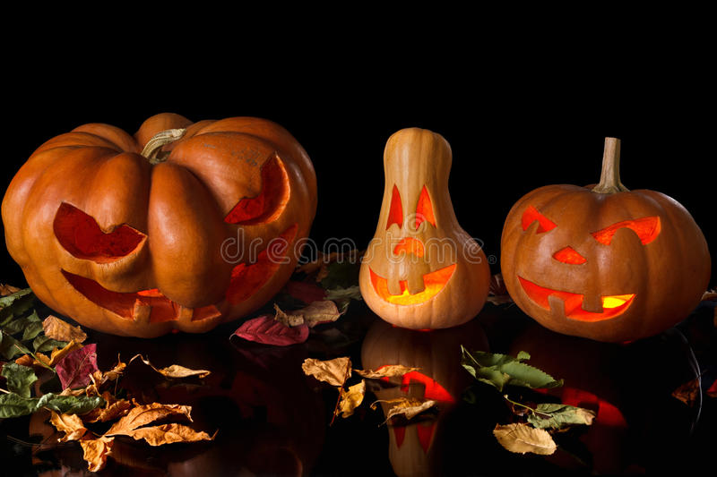 Spooky pumpkin halloween. Spooky Halloween pumpkin with fallen leaves, a terrible fire and reflections. Isolated on black background stock images