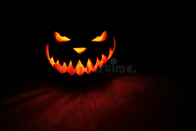 Spooky pumpkin Halloween. With fire light on black background stock images