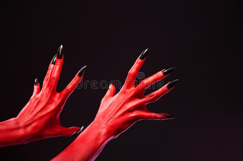 Spooky red devil hands with black nails, real body-art royalty free stock photography