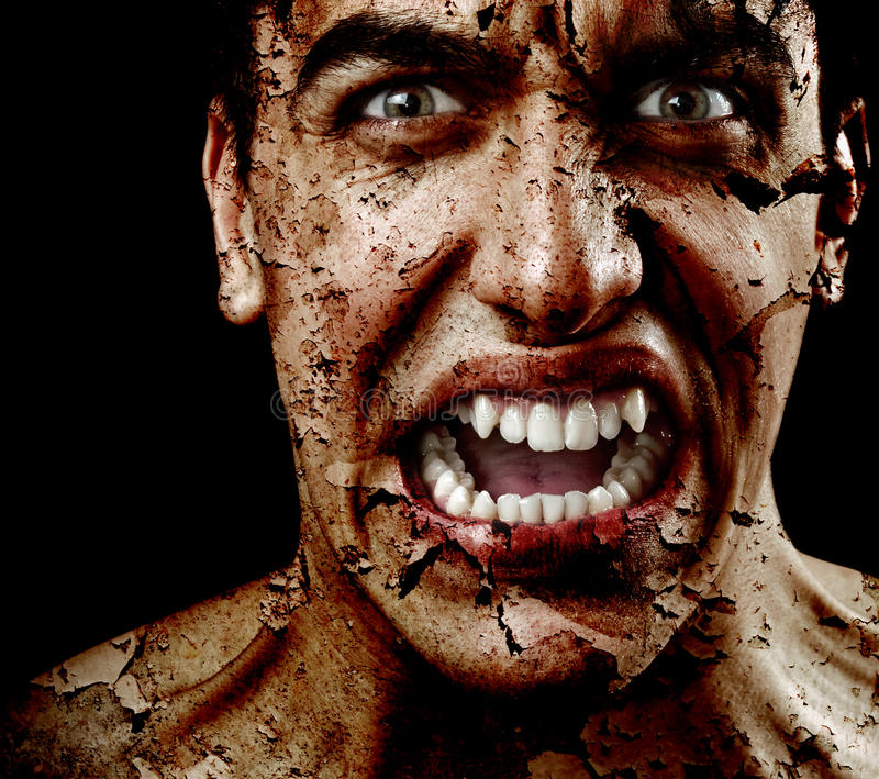 Spooky scary man with aged cracked peeling skin. Spooky sinister man with aged cracked peeling skin royalty free stock images