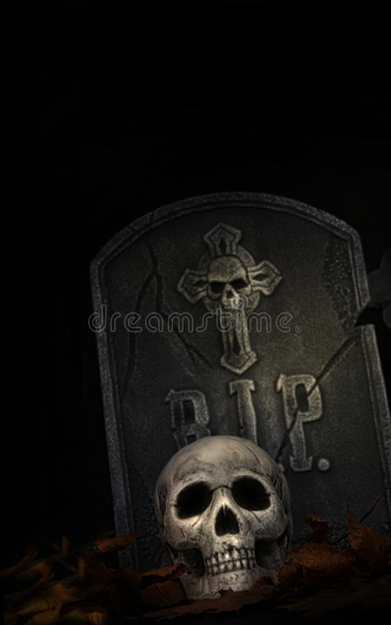 Spooky tombstone with skull on black. Background royalty free stock image