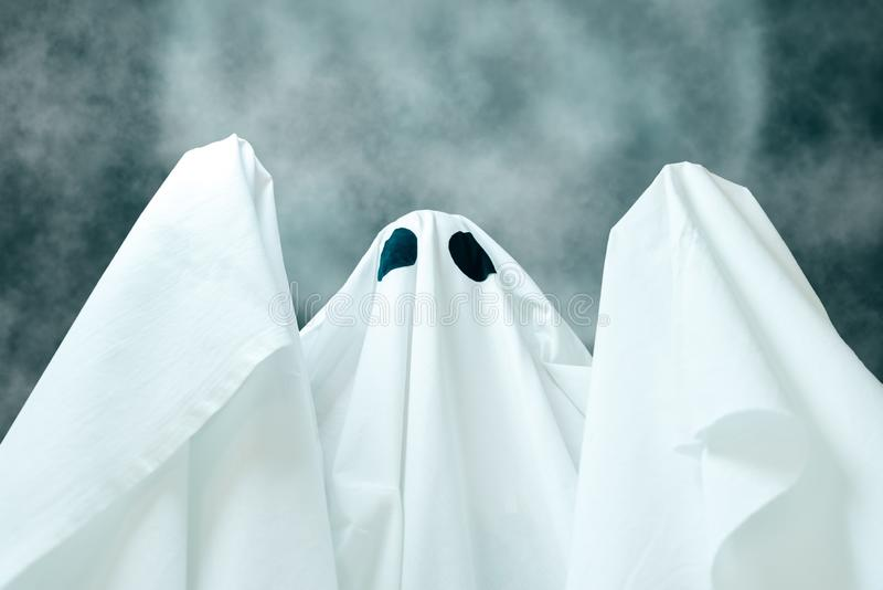 Spooky white ghost in Halloween night. Spooky white ghost with black eyes on background of full moon Halloween night stock photos