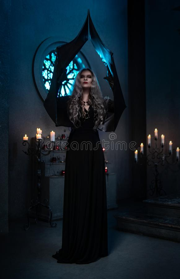Spooky woman in witch costume posing with raised arms royalty free stock photo
