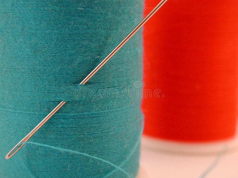 Spool of blue thread with needle