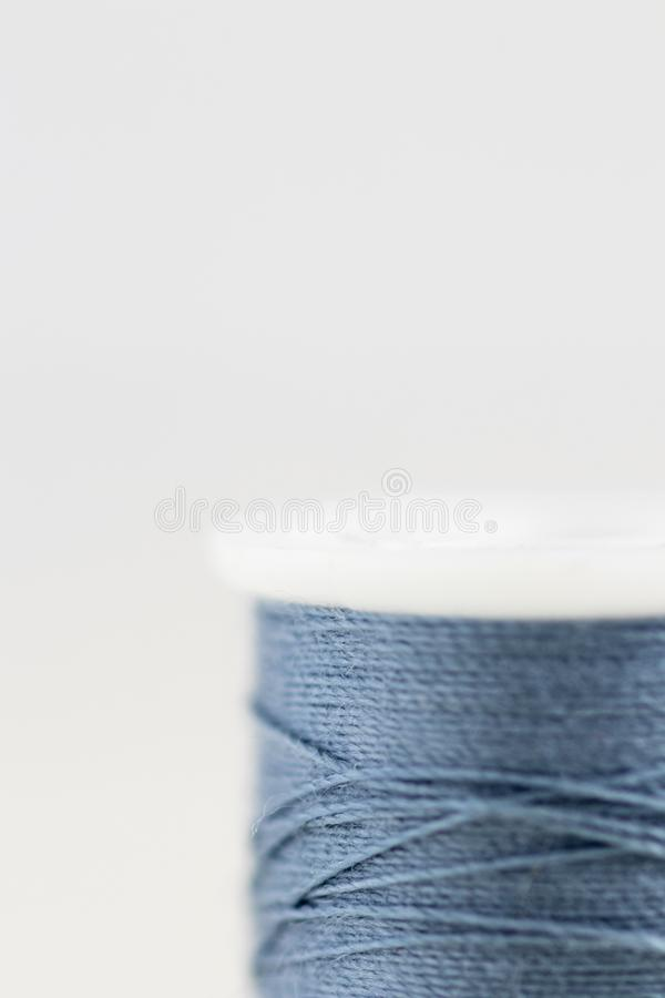 Spool of blue thread with very limited focus on white background. royalty free stock photos