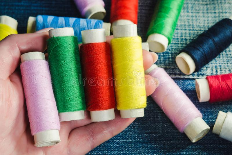 Spool of green, red, pink and yellow sewing thread in a female hand against the background of other spools of thread on denim. Spool of green, red, pink and royalty free stock images