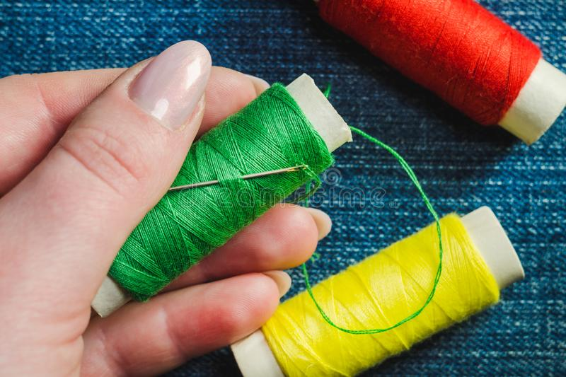 Spool of green sewing thread and a needle in a female hand against the background of other spools of thread on denim royalty free stock photo