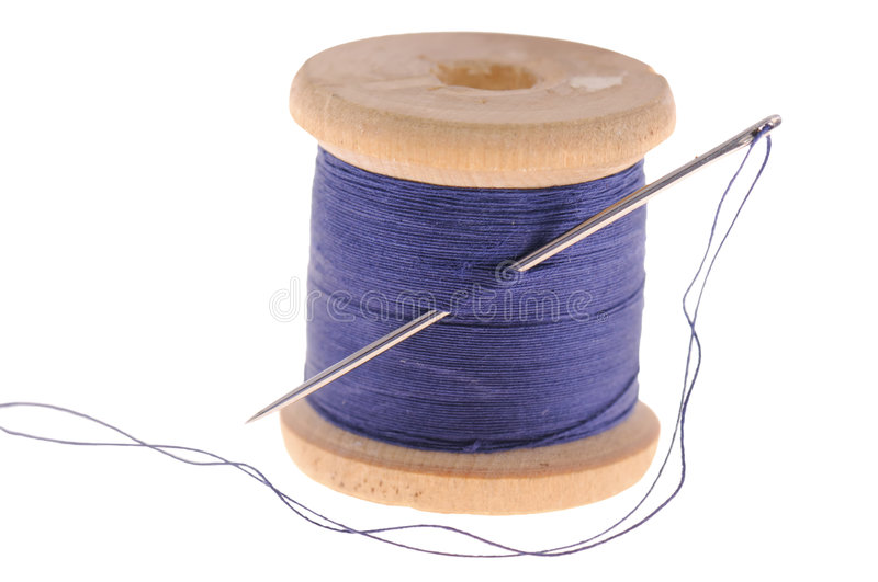 Spool of thread and sewing needle stock images