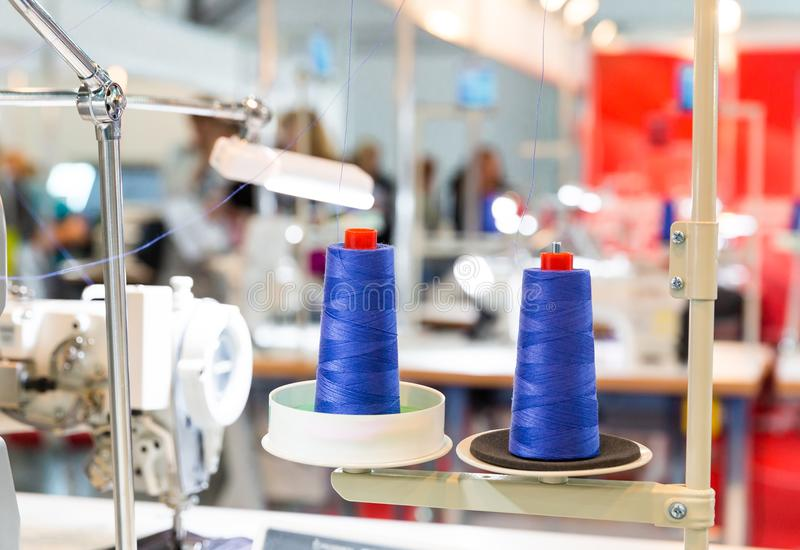 Spools of blue threads on sewing machine, factory stock photography