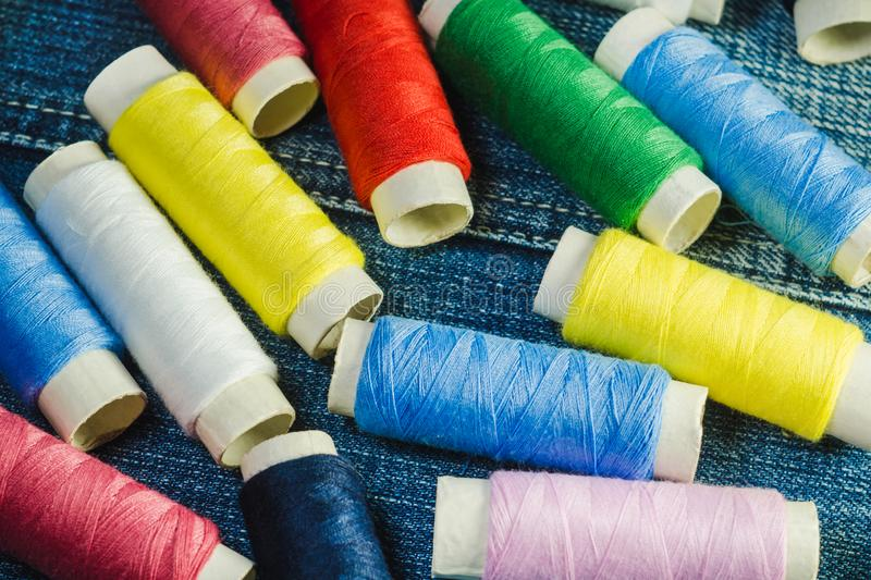 Spools of blue,white, pink, red and green sewing thread on blue denim.  royalty free stock photography