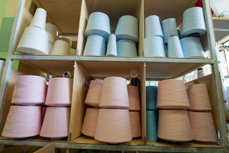 Pastel color thread spools at knitting factory view. Spools with different pastel color thread on shelves at knitting factory shot royalty free stock photo