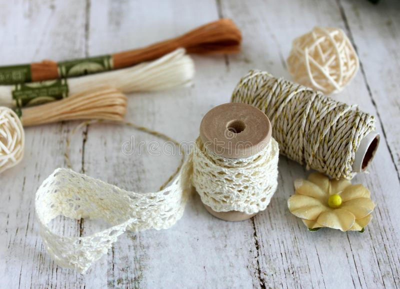 Spools with lace trim and baker`s twine. Laces and trims. Crafting and sewing supplies. Embroidery threads. royalty free stock image
