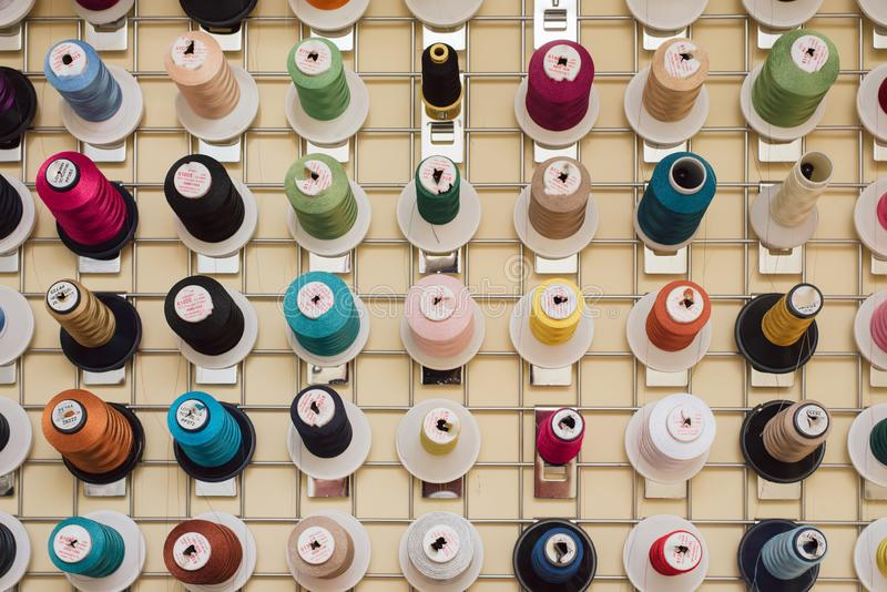 Spools of thread hanging in a tailor shop. Skeins for sewing machine hang in a sewing shop stock photo