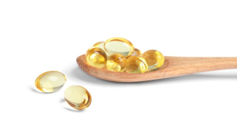 Spoon with cod liver oil pills stock photos