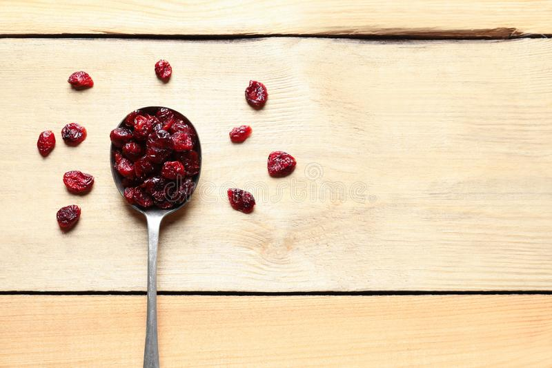 Spoon of cranberries on wooden background, top view royalty free stock image