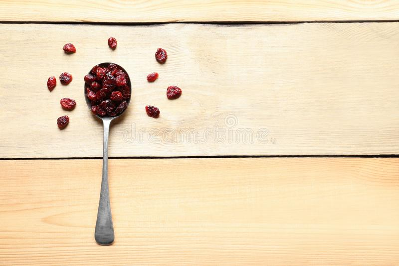 Spoon of cranberries on wooden background. Dried fruit as healthy snack stock photo