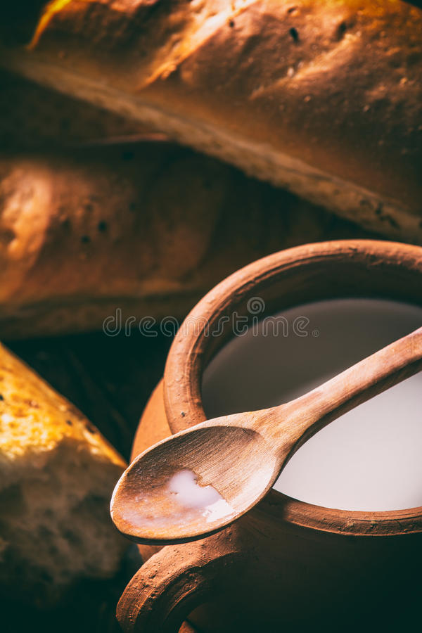 Spoon with drips milk in hand royalty free stock images
