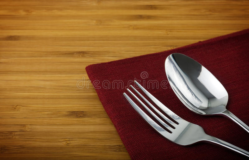 Spoon and fork. Stainless spoon and fork on linen napkin royalty free stock photos